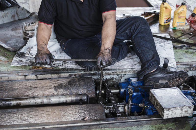 repairman holding a wrench and tighten and during maintenance work of machine royalty free stock photography