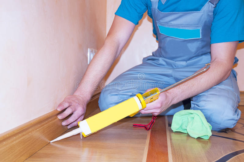 Repairman Installing Skirting Board Oak Wooden Floor with Caulking Gun Silicone. From Cartridge. Flooring with Wooden Batten Repair royalty free stock photography