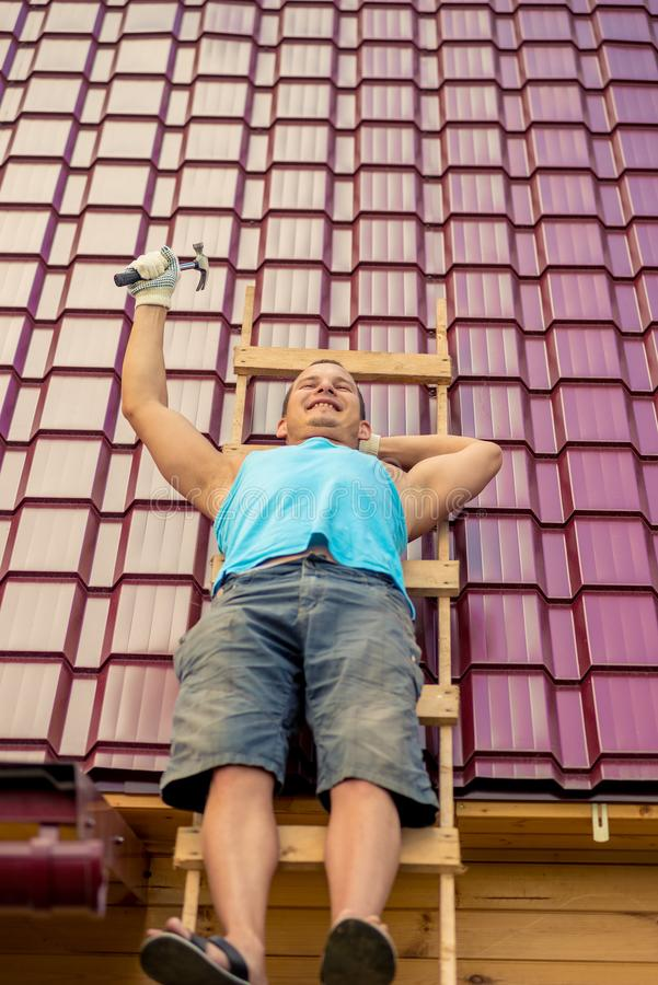 Repairman on a ladder on the roof while resting stock image