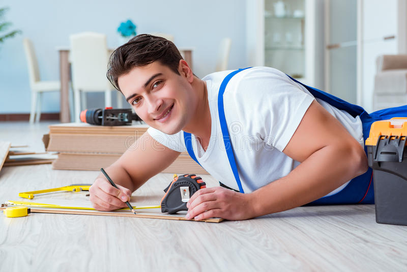 The repairman laying laminate flooring at home stock photography