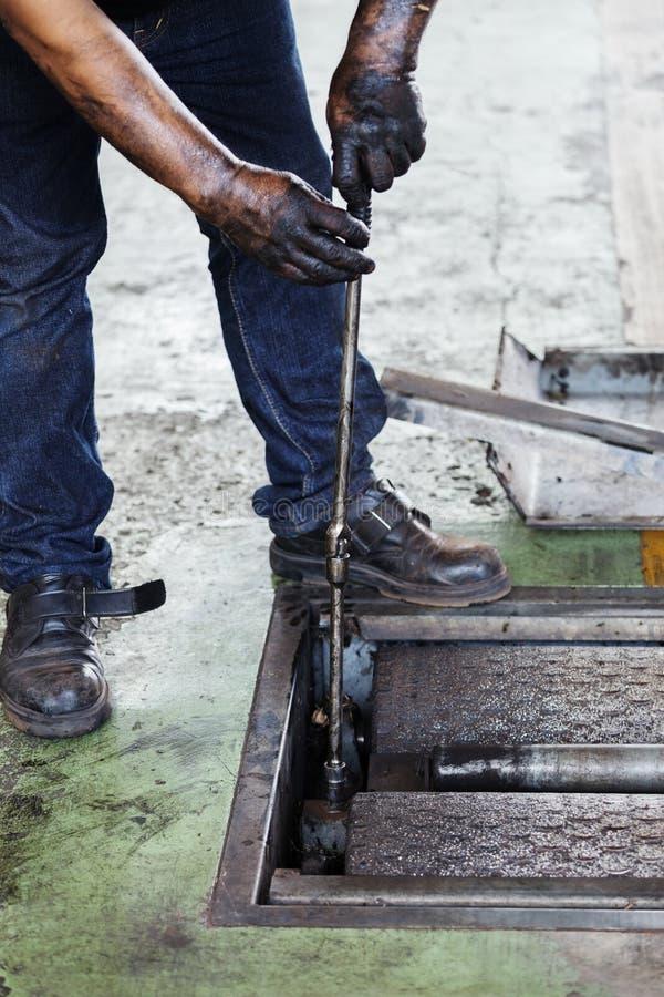 Repairman during maintenance work of machine royalty free stock image