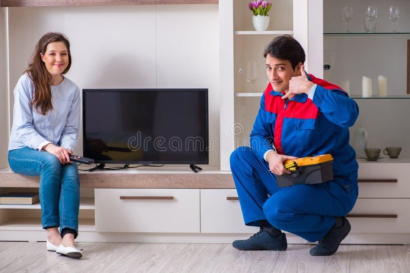 Repairman naprawia tv w domu fotografia stock
