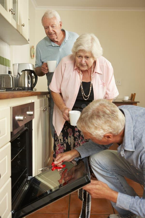Repairman naprawiania kuchenka W Starszej pary kuchni zdjęcia royalty free