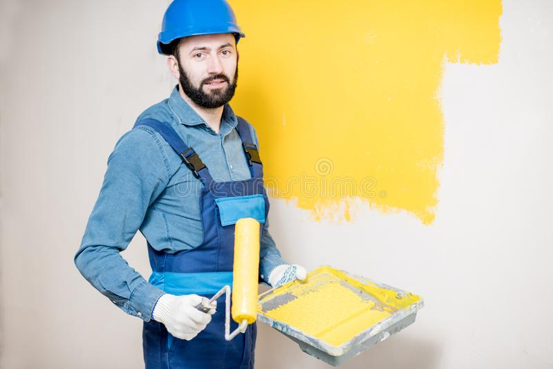 Repairman painting wall. Portrait of a handsome painter in working uniform painting wall with yellow paint royalty free stock photo