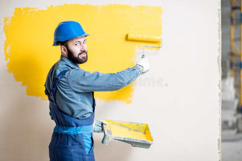 Repairman painting wall. Portrait of a handsome painter in working uniform painting wall with yellow paint stock photos