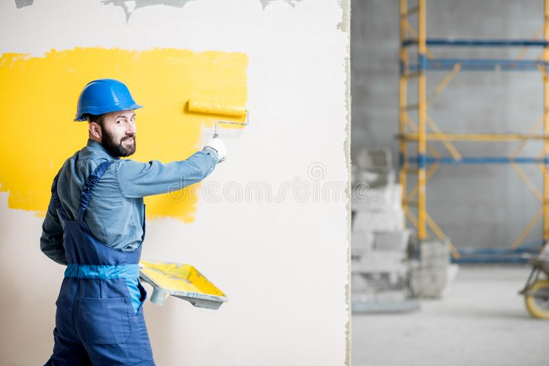 Repairman painting wall. Portrait of a handsome painter in working uniform painting wall with yellow paint stock images