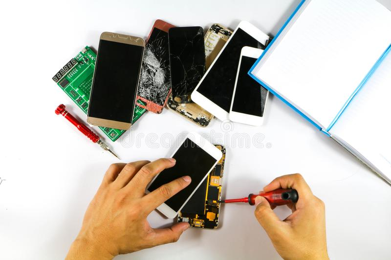 At mobile phone shop. Mobile phone repair technicians are speeding up repairing the phone of the customer with many number of item royalty free stock photography