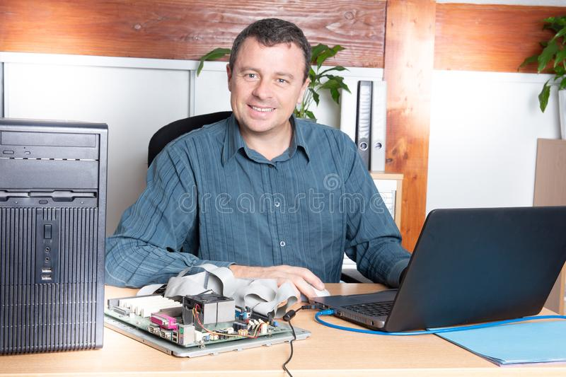 Repairman professional repair computer with laptop royalty free stock photos