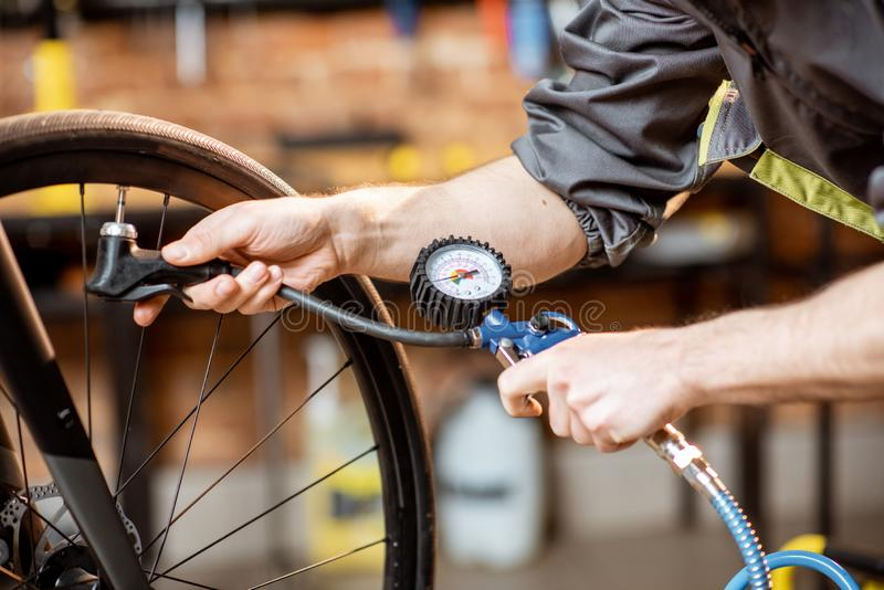 Repairman pumping wheels of the bicycle indoors stock image