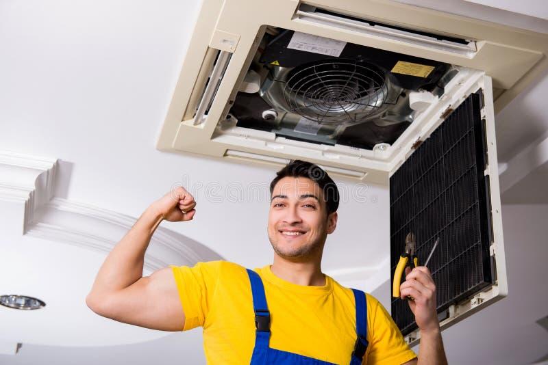 The repairman repairing ceiling air conditioning unit. Repairman repairing ceiling air conditioning unit royalty free stock images