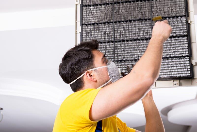 The repairman repairing ceiling air conditioning unit. Repairman repairing ceiling air conditioning unit royalty free stock photo
