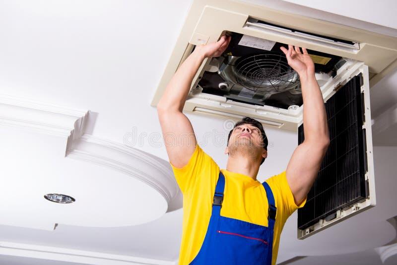 The repairman repairing ceiling air conditioning unit. Repairman repairing ceiling air conditioning unit stock images