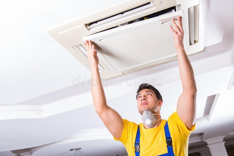 The repairman repairing ceiling air conditioning unit. Repairman repairing ceiling air conditioning unit stock photo