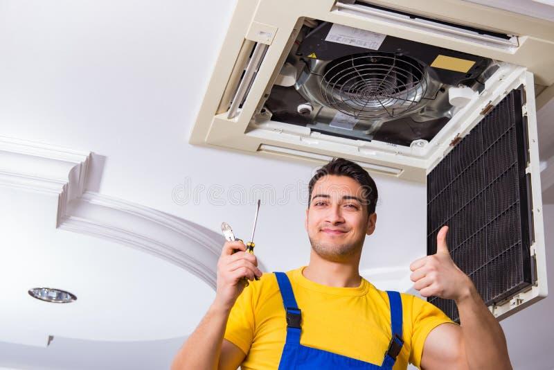 The repairman repairing ceiling air conditioning unit. Repairman repairing ceiling air conditioning unit stock image