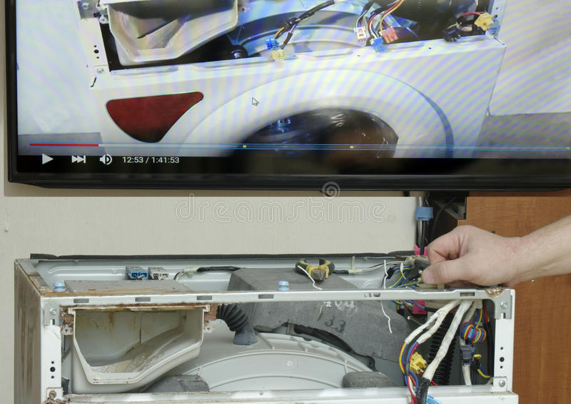 Repairman is repairing a washing machine royalty free stock image