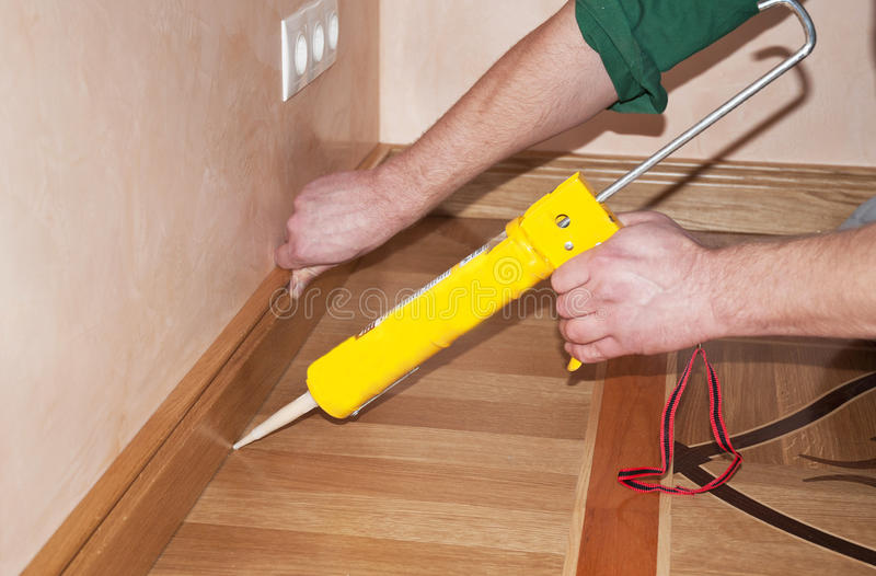 Repairman's hands Installing Skirting Board Oak Wooden Floor with Caulking Gu. N Silicone from Cartridge. Flooring with Wooden Batten Repair stock photo