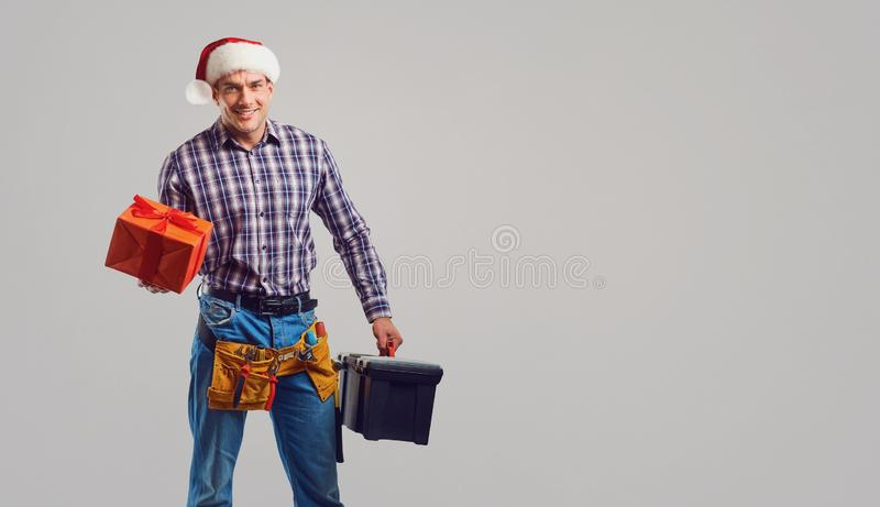 Repairman in Santa hat with a gift on a gray background. Repairman in Santa hat with a gift in special clothes with working tools on a gray background in stock photography