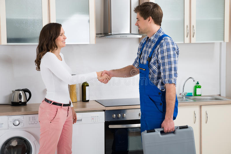 Repairman Shaking Hands With Woman royalty free stock photo