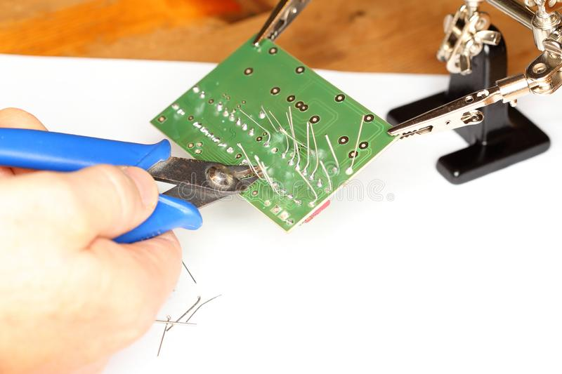 Repairman with side cutter is working. On green electronic device royalty free stock image