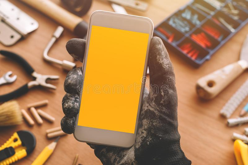 Repairman smart phone app, handyman holding mobile phone in hand royalty free stock photo