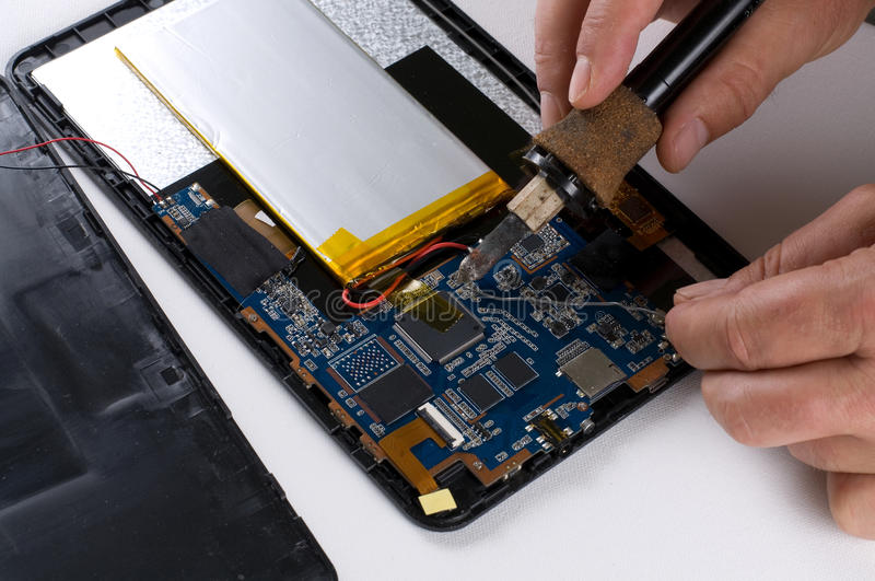 Repairman Soldering Electronic Device. Close up image of a repairman soldering an electronic device royalty free stock photos
