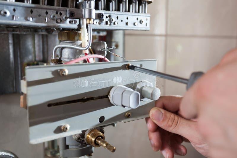 Repairman som justerar gasvattenvärmeapparaten royaltyfri fotografi