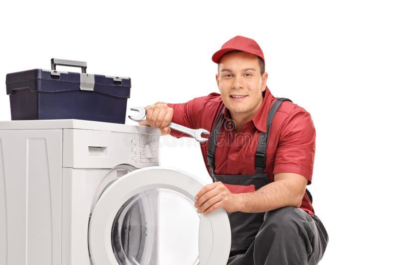 Repairman som poserar vid en tvagningmaskin royaltyfri fotografi