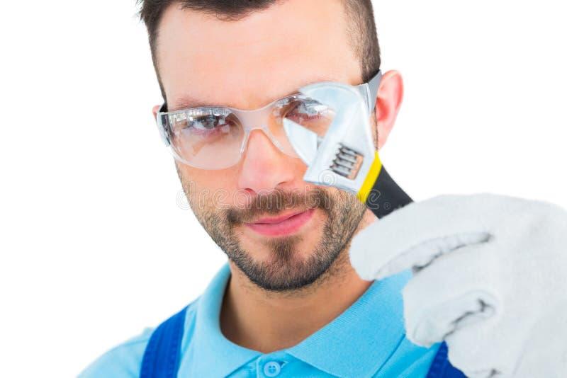 Repairman som ser till och med den justerbara skiftnyckeln arkivfoto