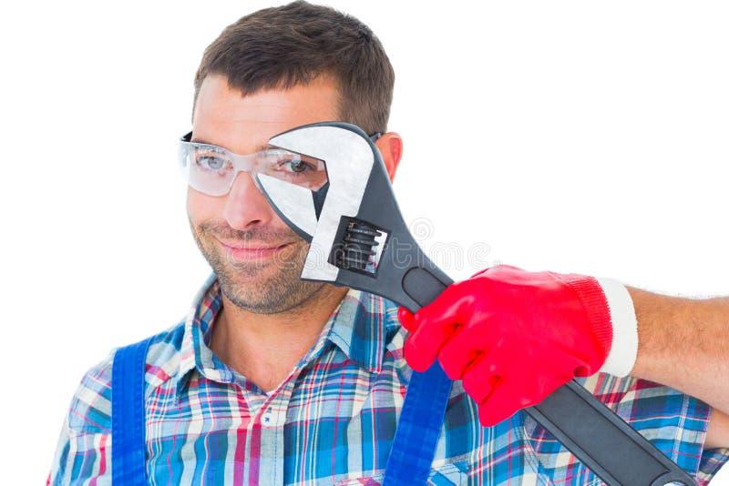 Repairman som ser till och med den justerbara skiftnyckeln fotografering för bildbyråer
