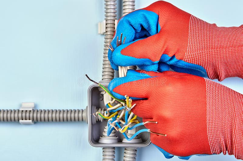 Repairman tightens in wires protective gloves royalty free stock photography