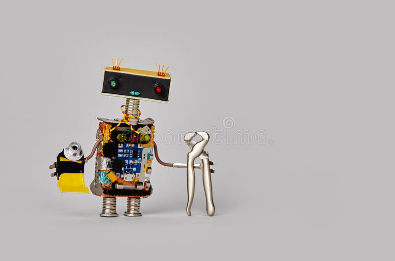 Repairman toy robot with tongs pliers and tube of glue. Friendly service worker, funny head colorful eyes, electronic stock images