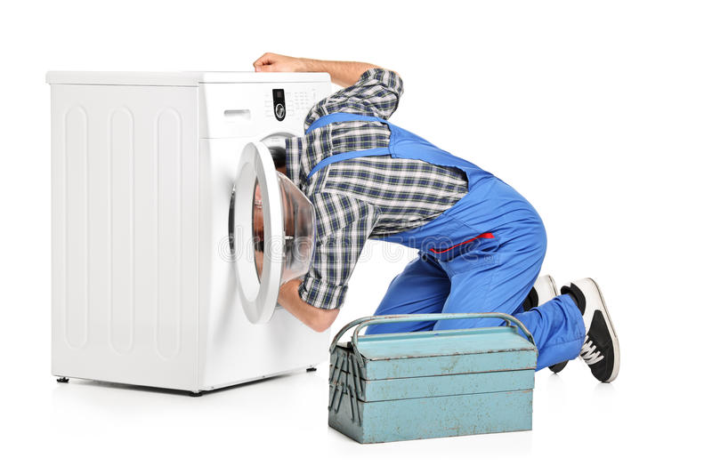Repairman trying to fix a washing machine. A repairman trying to fix a washing machine isolated on white background stock photos