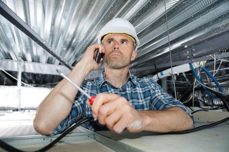 Repairman używa telefon haczy w górę władza kabli zdjęcia stock