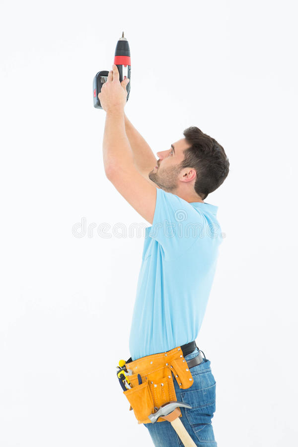 Repairman using hand drill. Side view of repairman using hand drill against white background stock photos