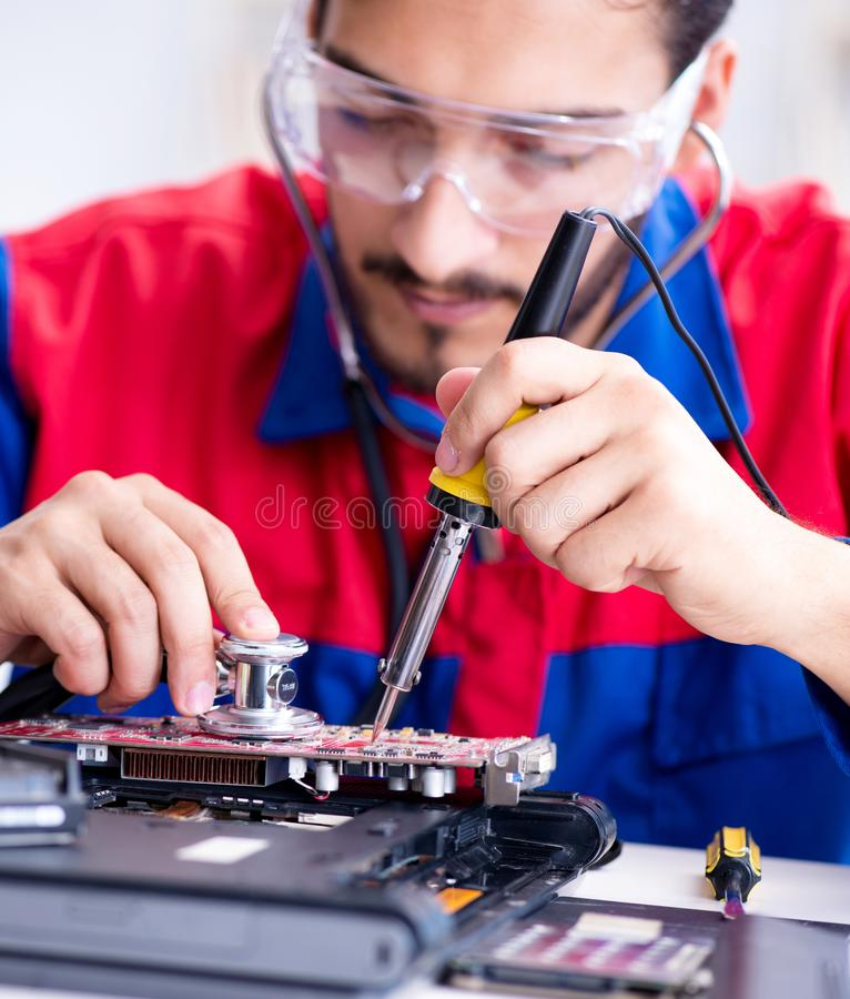 Repairman working in technical support fixing computer laptop tr. Oubleshooting royalty free stock photo