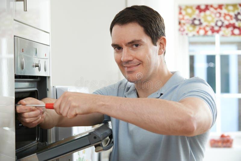 Repairman Załatwia Domowego piekarnika W kuchni zdjęcia royalty free