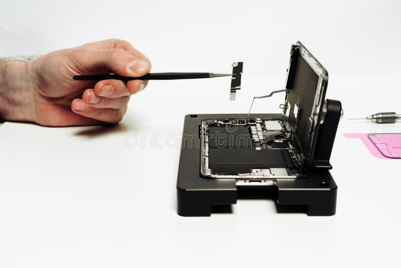 Repairmanen monterar den demonteraa öppna smartphonen royaltyfria foton
