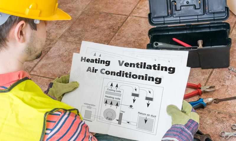 Repairmanen ser dokumentation av HVAC royaltyfri foto