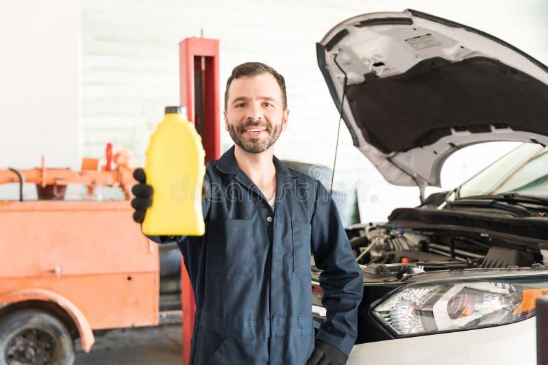 Repairmanen Showing Motor Oil kan i auto reparation shoppa royaltyfri foto