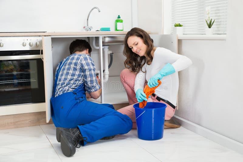 RepairmanFixing Pipe While kvinna som pressar den våta torkduken arkivfoto