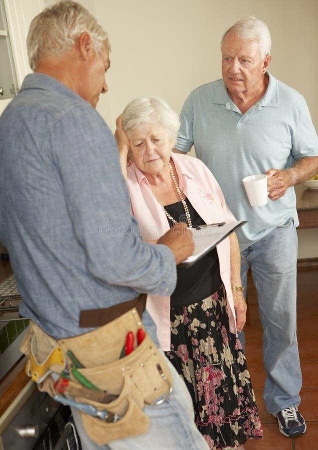 RepairmanGiving Senior Couple bedömning för reparation arkivbilder