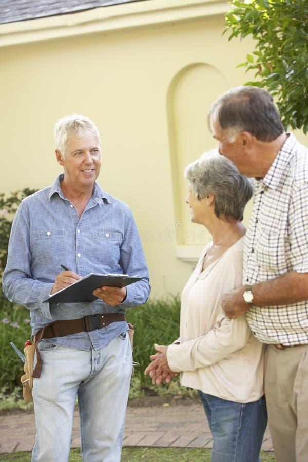RepairmanGiving Senior Couple bedömning för takreparation arkivfoton