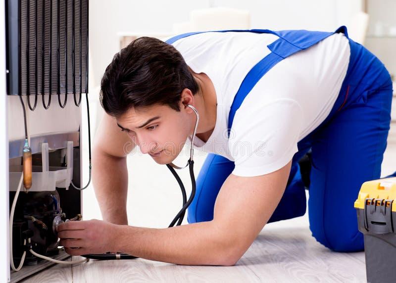 Repairmanleverant?r som reparerar kylen i DIY-begrepp royaltyfria foton