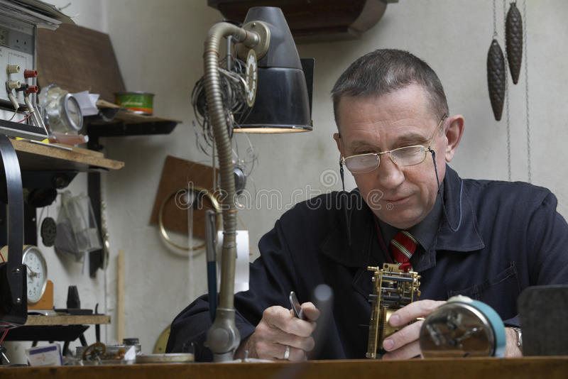 RepairmanWorking On An gammal klocka arkivbilder