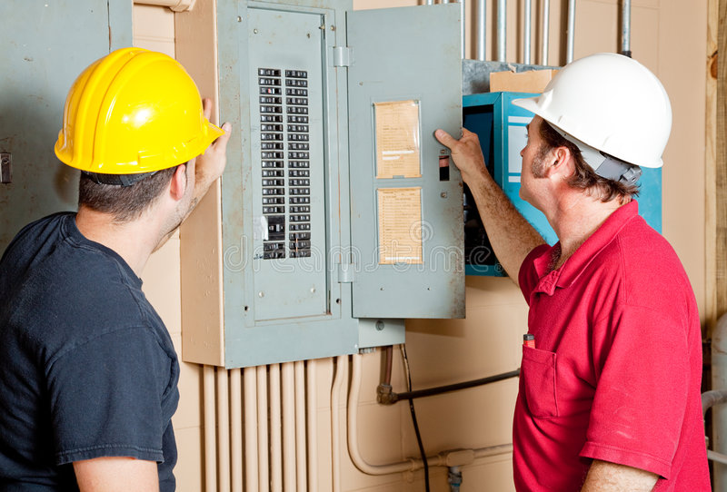 Repairmen Examine Electrical Panel. Electricians examining a circuit breaker panel in an industrial setting royalty free stock photos