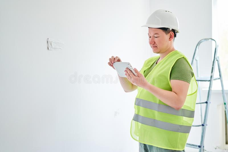 Repairs in the apartment, a man in a green vest and a white helmet is in a white room with a tablet in his hands royalty free stock photography