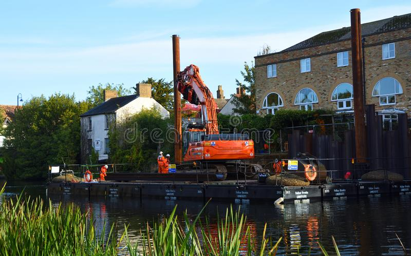 Repairs to the riverbank of the River Great Ouse at St Neots Cambridgeshire, Equipment on floating pontoon being used to drive in. ST NEOTS, CAMBRIDGESHIRE stock photos