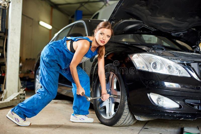 repairshop的女孩技工关闭汽车前轮  库存图片