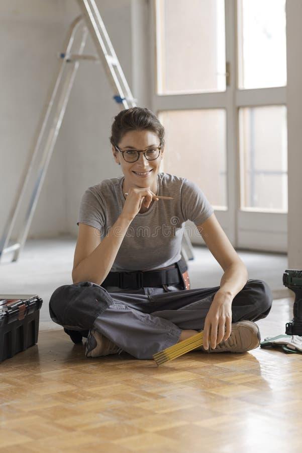Repairwoman che si siede sul pavimento e sulla posa immagine stock libera da diritti