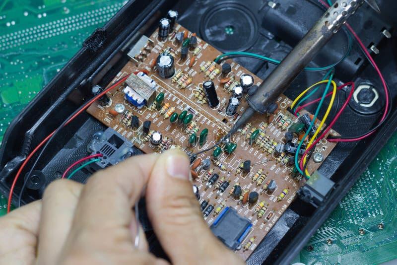 Reparação do técnico eletrônica da placa de circuito do ` s do computador por ferros de solda imagem de stock